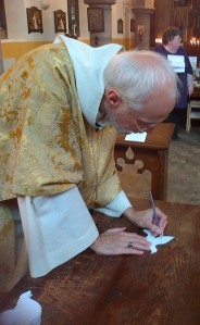 The Bishop of Manchester decorates a paper peace dove, appropriately choosing a purple pencil to do so!
