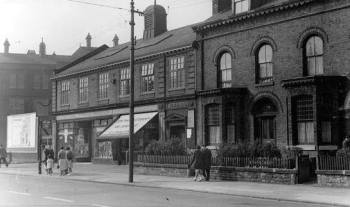 The detached clasroom for older children of the school was above the shop in this photo (note the Gaskell building in the background)