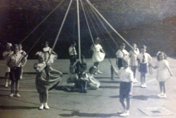 Boys and girls enjoyed dancing round the maypole in the playground.